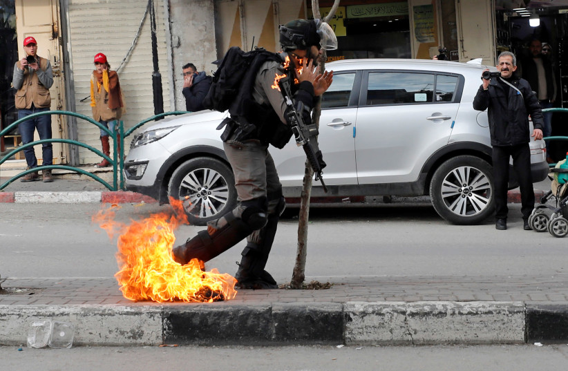 Israeli border policeman is on fire as he is hit with a molotov cocktail thrown by Palestinian demonstrators, Feb. 3, 2020 (photo credit: MUSSA ISSA QAWASMA/REUTERS)