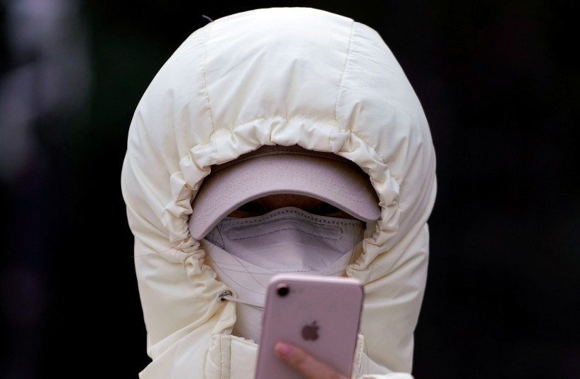A woman wearing a mask checks her mobile phone in Shanghai, China January 29, 2020 (photo credit: REUTERS/ALY SONG)