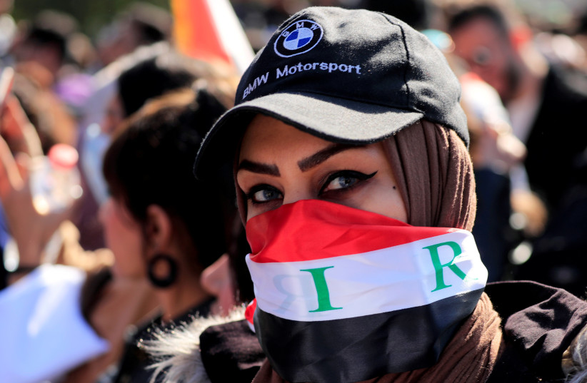 An Iraqi university student covers her face with Iraqi flag as she protests to express her rejection of the newly appointed Prime Minister of Iraq, Mohammed Tawfiq Allawi, during ongoing anti-government protests in Baghdad (photo credit: REUTERS)