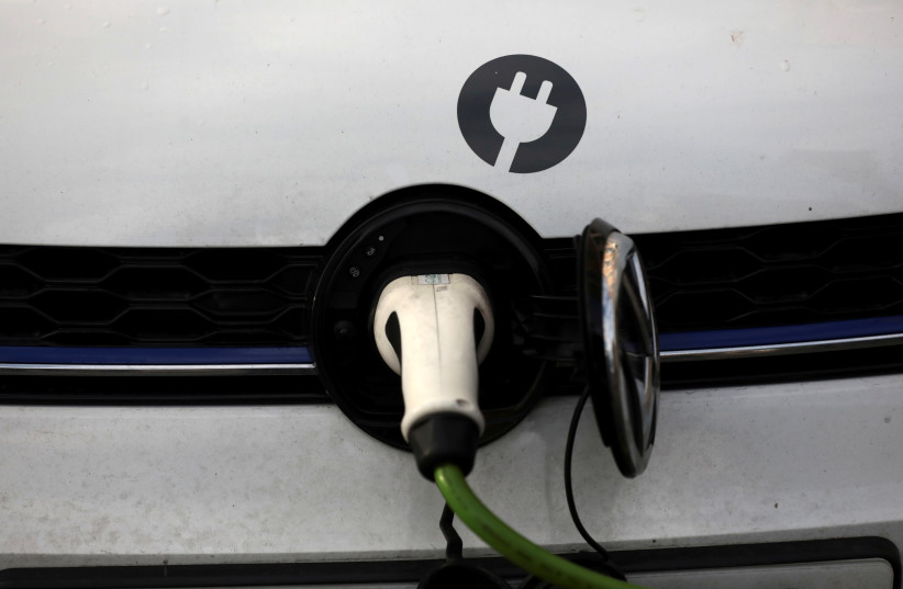 A car is plugged in at a charging point for electric vehicles in London (photo credit: REUTERS)