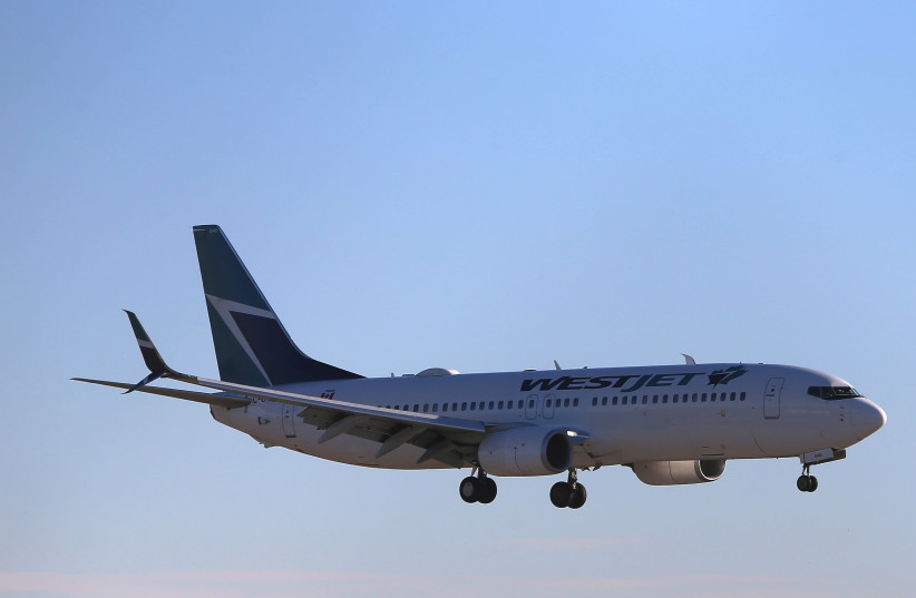 A WestJet Boeing 737-800 airplane lands at Vancouver's international airport in Richmond, British Columbia, Canada, February 5, 2019 (photo credit: REUTERS/BEN NELMS)
