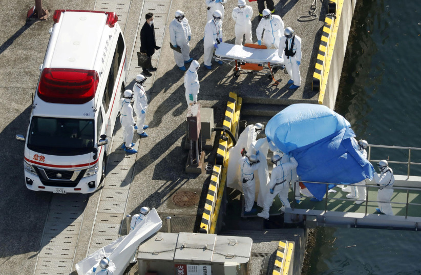 Officers in protective gear escort a person who was on board cruise ship Diamond Princess and was tested positive for coronavirus, after the person is transferred to a maritime police base in Yokohama (photo credit: REUTERS)