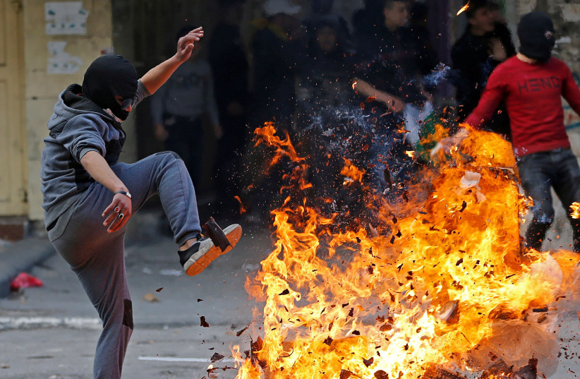 A Palestinian reacts next to a fire during a protest against the U.S. President Donald Trump's Middle East peace plan, in Hebron in the Israeli-occupied West Bank February 6, 2020 (photo credit: REUTERS/MUSSA QAWASMA)