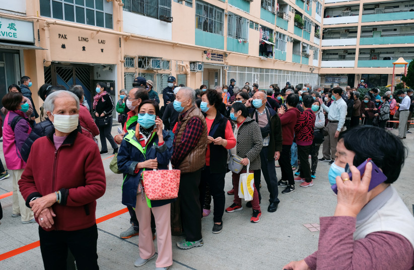 Elderly people queue up for free surgical masks from a convenience store, following the outbreak of a new coronavirus, in Hong Kong, China February 7, 2020. (photo credit: REUTERS/TYRONE SIU)