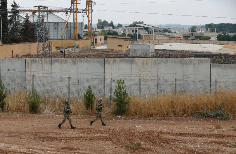 Turkish soldiers patrol along a wall on the border line between Turkey and Syria, in the Turkish border town of Ceylanpinar, in Sanliurfa province, Turkey, October 29, 2019 (photo credit: REUTERS/KEMAL ASLAN)