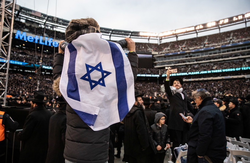 Orthodox Jews sing and dance during the 13th Siyum HaShas at the MetLife Stadium in East Rutherford, New Jersey, on January 1 (photo credit: REUTERS)