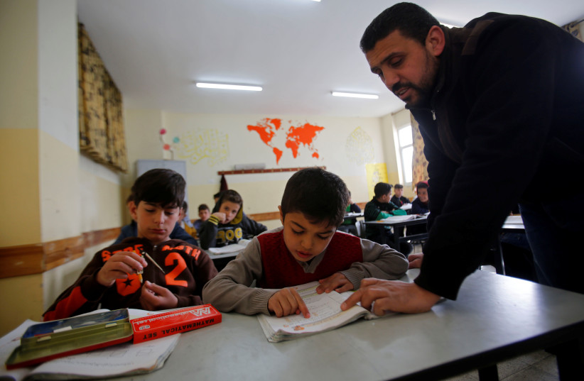 Palestinian boy Zain Idrees attends a lesson inside a classroom in a school, in Hebron, in the West Bank April 25, 2019 (photo credit: REUTERS/MUSSA QAWASMA)