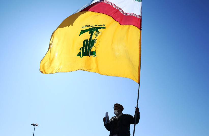 An Iranian carries the Iranian and Hezbollah flags during the commemoration of the 41st anniversary of the Islamic revolution in Tehran, Iran February 11, 2020 (photo credit: NAZANIN TABATABAEE/WANA VIA REUTERS)