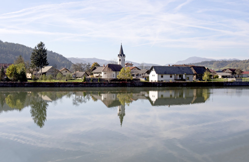 A CHURCH and houses in the small village of Kompolje, Slovenia reflect into the waters of the Sava River. This tranquil shot was actually taken from a fast-moving train. (photo credit: ILAN ROGERS)