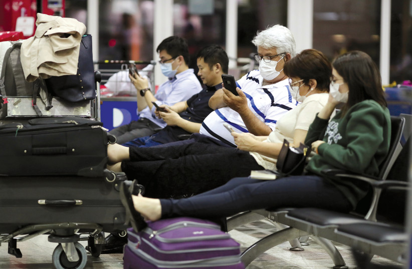 TRAVELLERS, WEARING masks as a precautionary measure to avoid contracting coronavirus, are seen at Guarulhos International Airport in Guarulhos, Sao Paulo state, Brazil.  (photo credit: REUTERS)