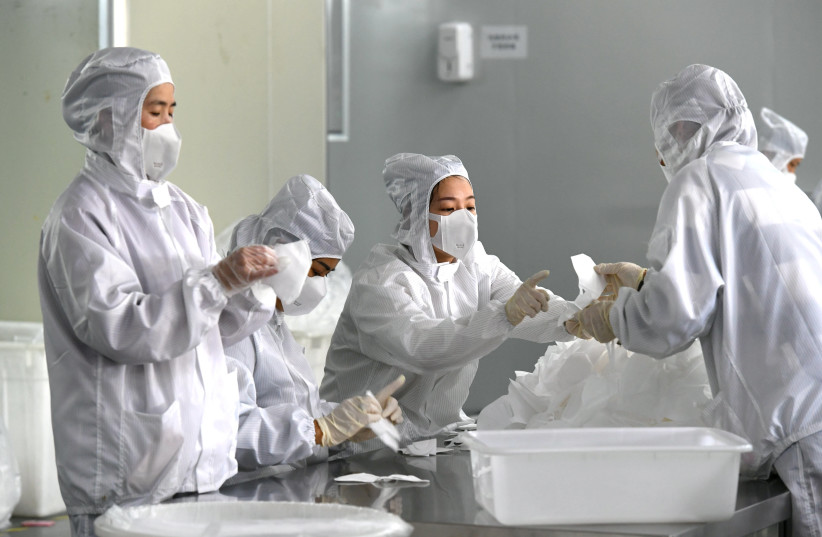 Employees work on a production line manufacturing face masks at a factory, as the country is hit by an outbreak of the novel coronavirus, in Fuzhou, Fujian province, China February 15, 2020 (photo credit: CNSPHOTO VIA REUTERS)