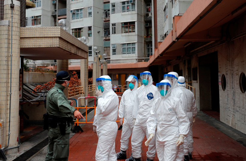 Police in protective gear wait to evacuate residents from a public housing building, following the outbreak of the novel coronavirus, in Hong Kong, China February 11, 2020 (photo credit: REUTERS/TYRONE SIU)