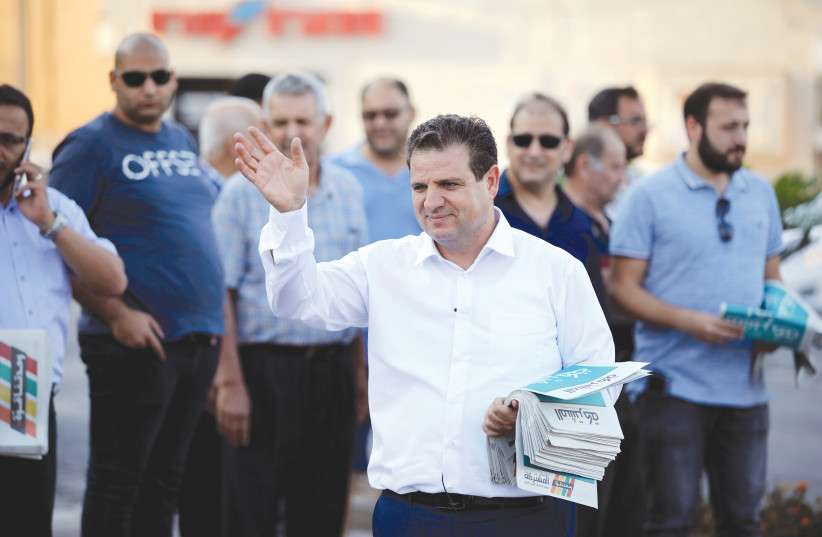 AYMAN ODEH, leader of the Joint List, gestures as he hands out pamphlets during an an election campaign event in Tira. (photo credit: REUTERS)