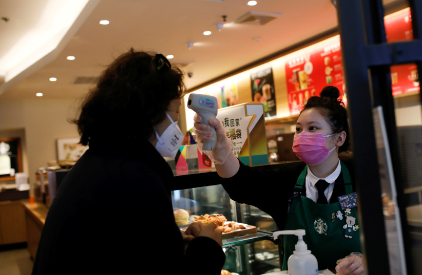 A worker uses a thermometer to check the temperature of a customer as she enters a Starbucks shop as the country is hit by an outbreak of the new coronavirus, in Beijing, China January 30, 2020. (photo credit: CARLOS GARCIA RAWLINS/ REUTERS)