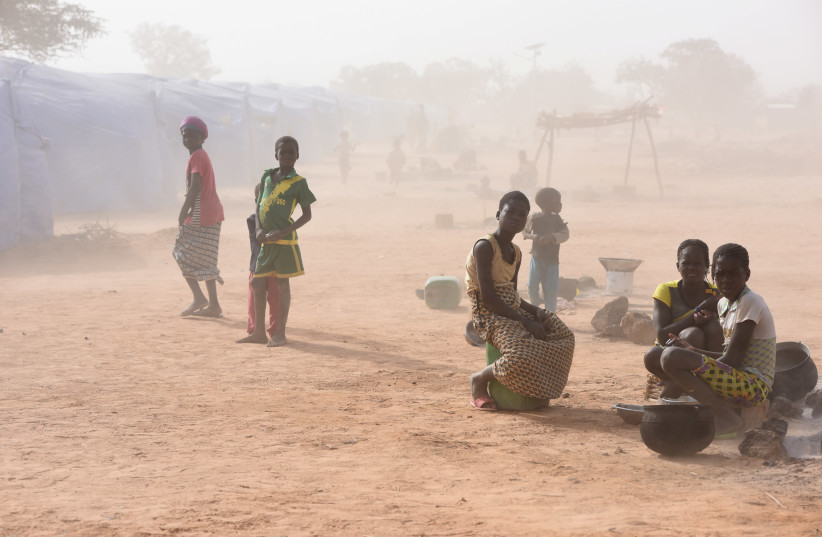 Displaced people, who fled from attacks of armed militants in Roffenega, are engulfed in dust as they sit at the camp built by the German Ngo HELP in Pissila (photo credit: REUTERS)