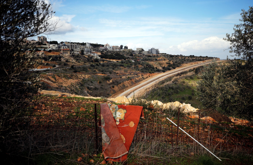 Carpet is seen hanging outside a family's home as a military road runs between the Arab-Israeli city of Umm al-Fahm and the Palestinian village of Anin in the West Bank near Jenin (photo credit: REUTERS)