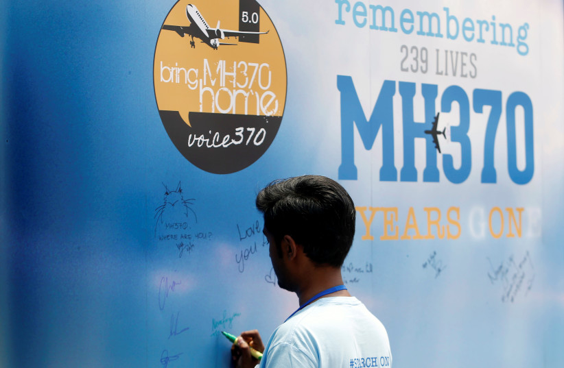 A man writes on a message board for passengers, onboard the missing Malaysia Airlines Flight MH370, during its fifth annual remembrance event in Kuala Lumpur (photo credit: REUTERS)