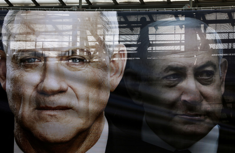 A banner depicts Benny Gantz, leader of Blue and White party, and Israel Prime minister Benjamin Netanyahu, as part of Blue and White party's campaign ahead of the upcoming election, in Tel Aviv, Israel February 17, 2020 (photo credit: AMMAR AWAD / REUTERS)