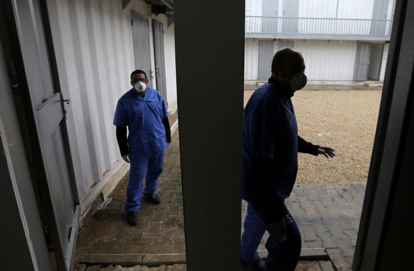 Palestinian health workers wearing protective masks walk in a quarantine zone installed by the ministry of health to test passengers returning from China for coronavirus, at Rafah border crossing in the southern Gaza Strip February 16, 2020. (photo credit: REUTERS/IBRAHEEM ABU MUSTAFA)
