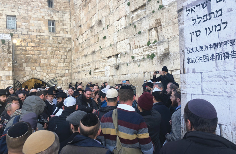 AT A MASS prayer service at the Western Wall on Sunday, worshipers pray for those affected by coronavirus. The Hebrew on the poster reads, 'The People of Israel prays for China.' (photo credit: YAAKOV LEHMAN)