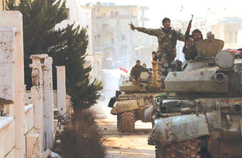 SYRIAN ARMY soldiers gesture last week in Kafr Hamra, in Syria's Aleppo province. (photo credit: SANA/REUTERS)