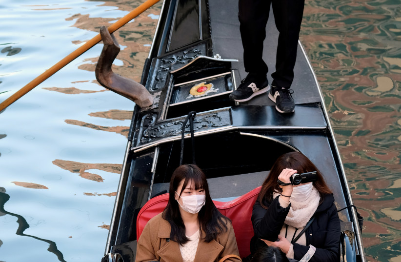 Tourists wearing protective masks travel on a gondola in Venice, Italy, February 7, 2020.  (photo credit: REUTERS)