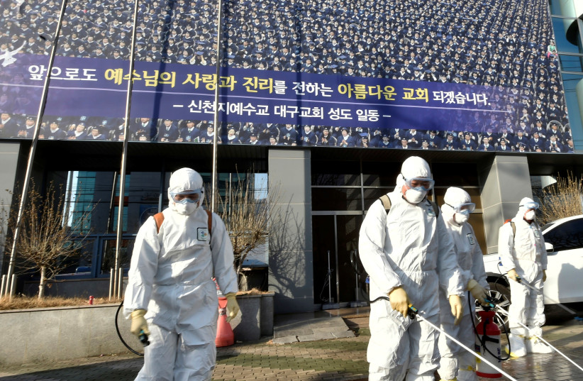 """Workers from a disinfection service company sanitize a street in front of a branch of the Shincheonji Church of Jesus the Temple of the Tabernacle of the Testimony where a woman known as """"Patient 31"""" attended a service in Daegu, South Korea, February 19, 2020 (photo credit: YONHAP VIA REUTERS)"""