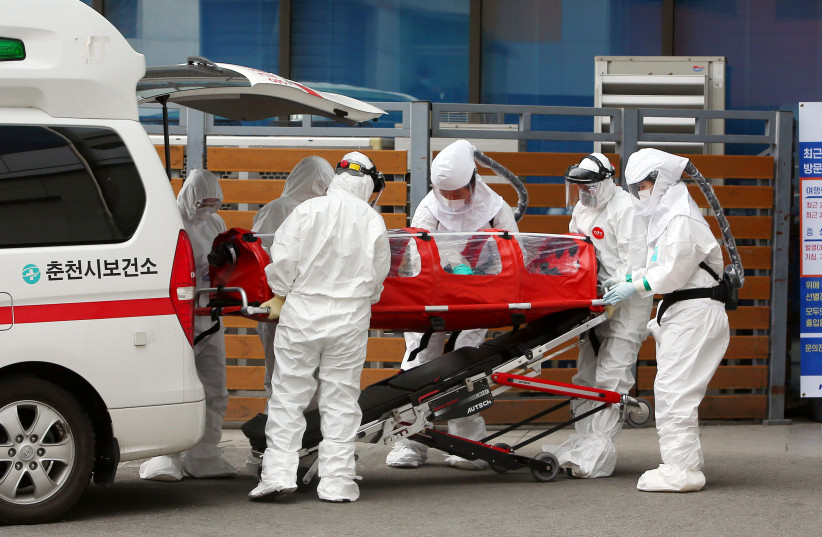 A confirmed coronavirus patient is wheeled to a hospital at Chuncheon, South Korea, February 22, 2020. (photo credit: YONHAP VIA REUTERS)