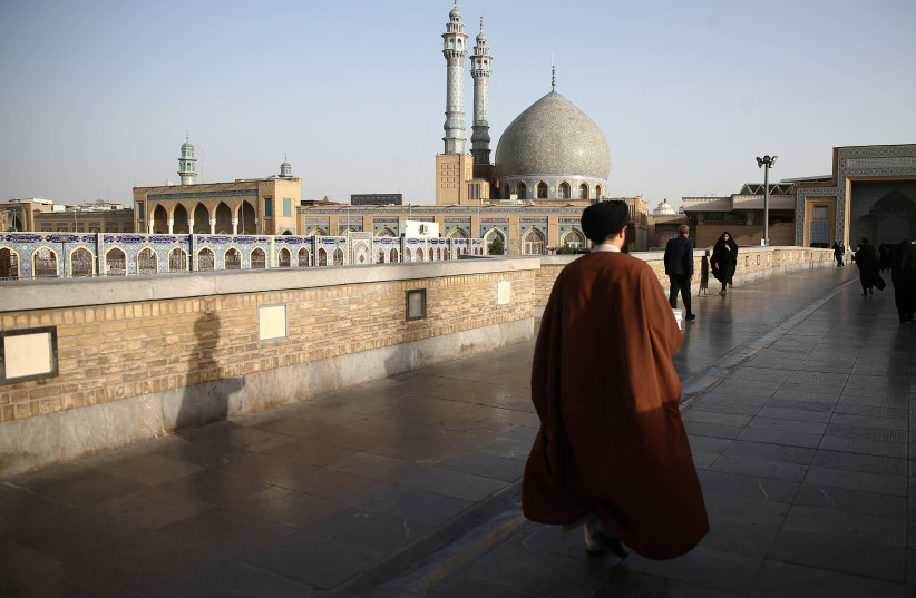 An Iranian cleric walks in front of the Shrine of Fatima Masumeh in Qom (photo credit: WANA NEWS AGENCY/REUTERS)