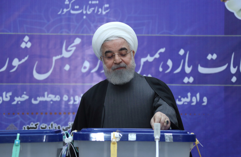 Iranian President Hassan Rouhani casts his vote at a polling station during parliamentary elections in Tehran, Iran February 21, 2020 (photo credit: REUTERS)