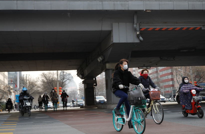 People wearing face masks ride bicycles and scooters on the street, as the country is hit by an outbreak of the new coronavirus, in Beijing, China February 24, 2020 (photo credit: REUTERS/CARLOS GARCIA RAWLINS)