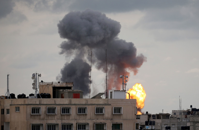 Flame and smoke are seen during an Israeli air strike in the southern Gaza Strip (photo credit: IBRAHEEM ABU MUSTAFA/REUTERS)