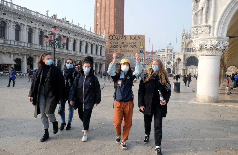 People wear protective face masks as they walk in St. Mark's square after the last days of Venice Carnival were cancelled due to coronavirus, in Venice (photo credit: REUTERS)