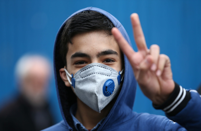An Iranian boy gestures as he wears protective mask to prevent contracting a coronavirus in Tehran (photo credit: REUTERS)