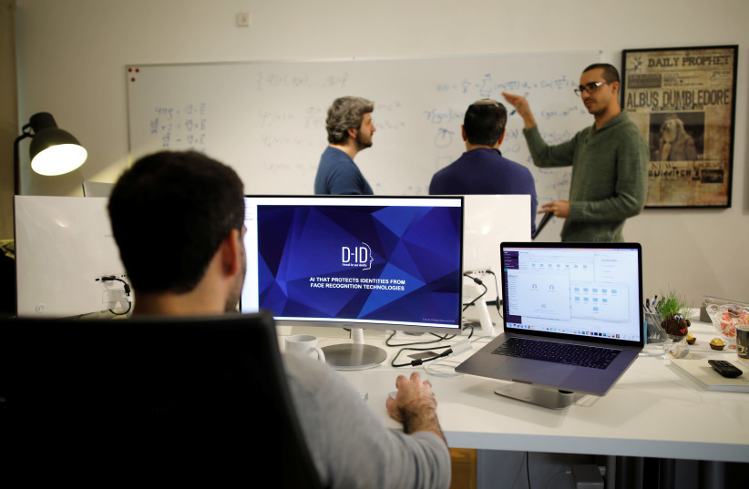 Employees of the D-ID startup company work at the company's office in Tel Aviv (photo credit: AMIR COHEN/REUTERS)
