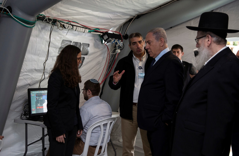 Israeli Prime Minister Benjamin Netanyahu arrives to a tent during his visit to the Chaim Sheba Medical Center at Tel Hashomer in Ramat Gan, Israel, for discussion on the coronavirus, February 19, 2020 (photo credit: HEIDI LEVINE / POOL / AFP)