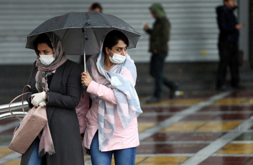 Iranian women wear protective masks to prevent contracting coronavirus, as they walk in the street in Tehran, Iran February 25, 2020. (photo credit: NAZANIN TABATABAEE/WANA VIA REUTERS)