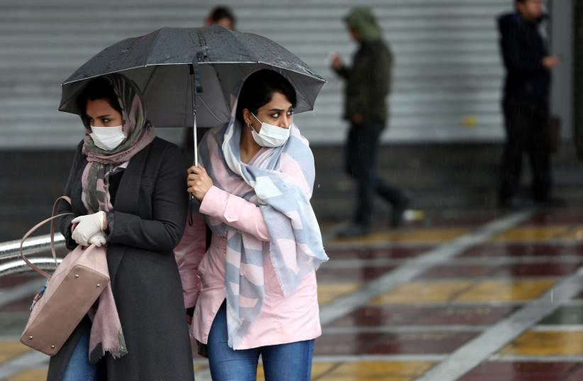 Iranian women wear protective masks to prevent contracting coronavirus, as they walk in the street in Tehran, Iran February 25, 2020. (photo credit: NAZANIN TABATABAEE/WANA VIA REUTERS)