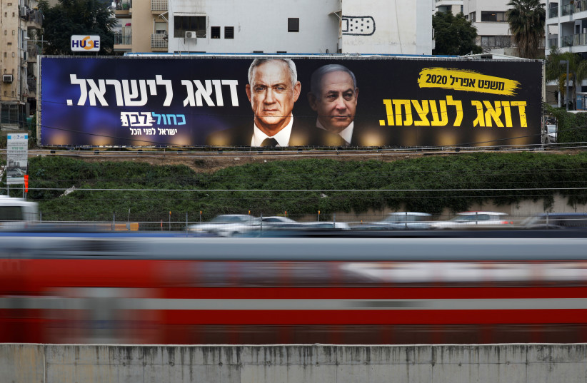 Traffic moves past a Blue and White party election campaign poster, depicting party leader Benny Gantz, and Israeli Prime Minister Benjamin Netanyahu, in Tel Aviv, Israel February 18, 2020 (photo credit: AMIR COHEN/REUTERS)