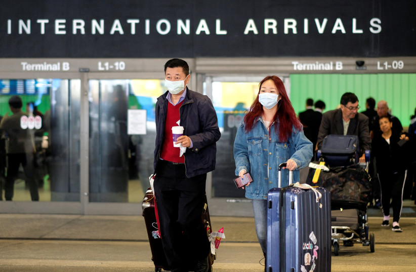 Passengers leave LAX after arriving from Shanghai, China, after a positive case of the coronavirus was announced in the Orange County suburb of Los Angeles, California, U.S., January 26, 2020 (photo credit: REUTERS/RINGO CHIU)
