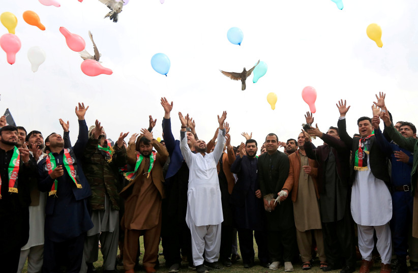 Afghan men celebrate in anticipation of the U.S-Taliban agreement to allow a U.S. troop reduction and a permanent ceasefire, in Jalalabad, Afghanistan February 28, 2020. Picture taken February 28, 2020 (photo credit: REUTERS/PARWIZ)