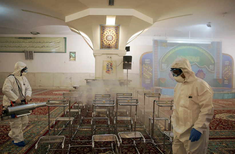 Members of the medical team spray disinfectant to sanitize indoor place of Imam Reza's holy shrine, following the coronavirus outbreak, in Mashhad, Iran February 27, 2020 (photo credit: REUTERS)
