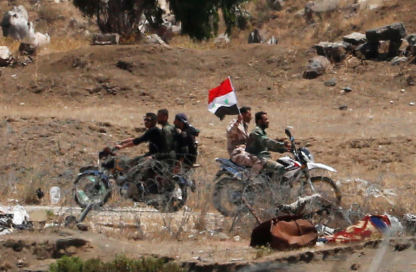 Uniformed men ride a motorbike as they carry a Syrian flag in Quneitra on the Syrian side of the ceasefire line between Israel and Syria, as seen from the Israeli-occupied Golan Heights (photo credit: REUTERS/AMMAR AWAD)