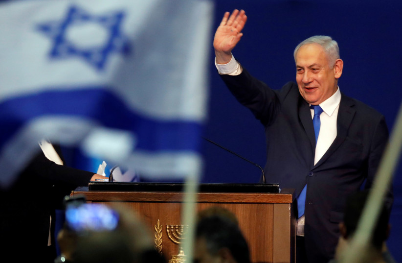 Prime Minister Benjamin Netanyahu waves to supporters following the announcement of exit polls in Israel's election at his Likud party headquarters in Tel Aviv on March 3, 2020.  (photo credit: AMIR COHEN - REUTERS)
