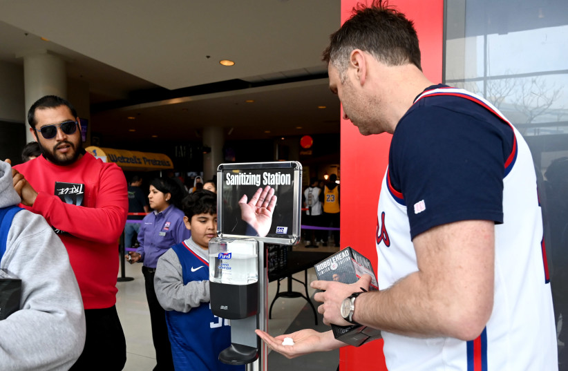 Fans use hand sanitizer as they enter Staples Center in California amid the coronavirus outbreak (photo credit: JAYNE KAMIN-ONCEA-USA TODAY SPORTS/REUTERS)