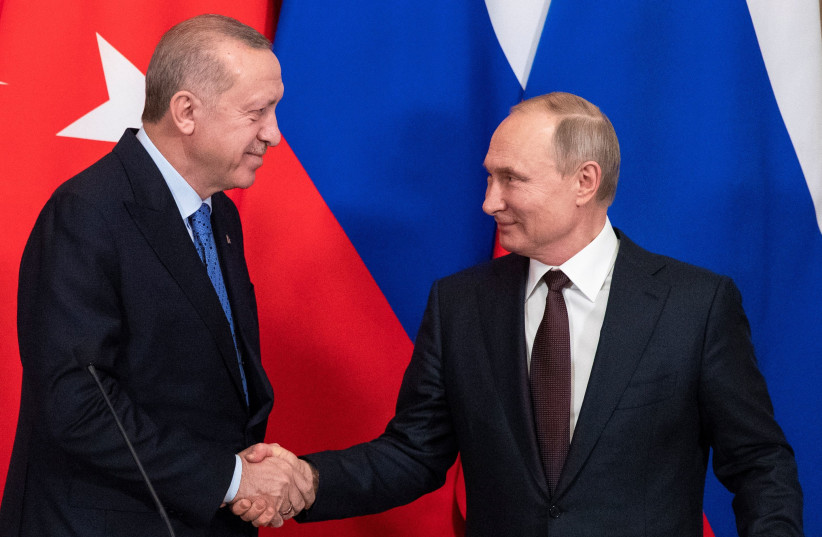 Russian President Vladimir Putin and Turkish President Tayyip Erdogan shake hands during a news conference following their talks in Moscow, Russia March 5, 2020.  (photo credit: PAVEL GOLOVKIN/POOL VIA REUTERS)