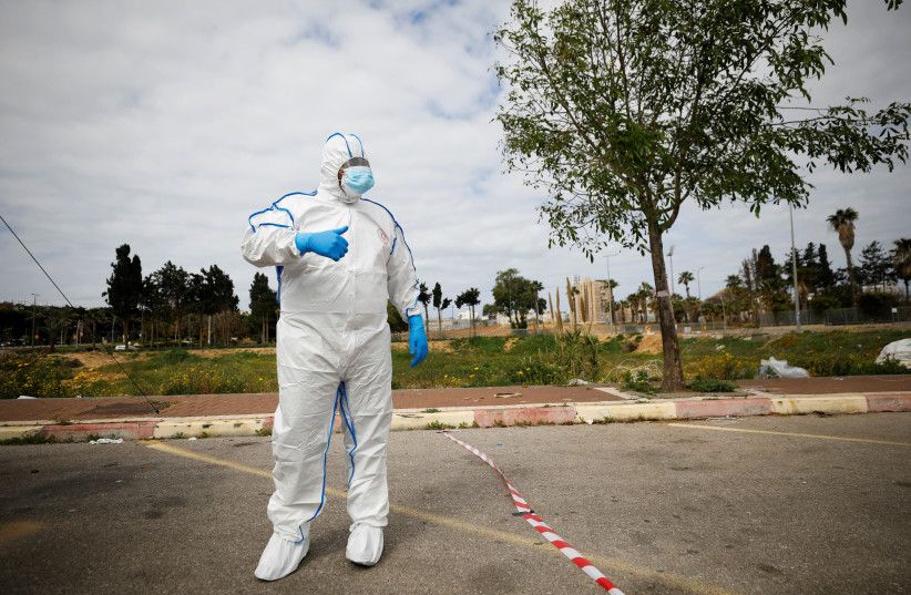 A paramedic wearing a protective suit stands near a special polling station set up by Israel's election committee so Israelis under home-quarantine, such as those who have recently travelled back to Israel from coronavirus hot spots, can vote in Israel's national election, in Ashkelon, Israel March  (photo credit: AMIR COHEN/REUTERS)