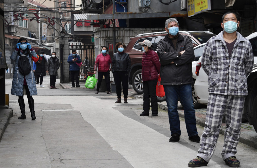 Residents line up to collect vegetables purchased through group orders at a residential area in Wuhan, the epicentre of the novel coronavirus outbreak, Hubei province, China March 5, 2020. (photo credit: REUTERS/STRINGER)