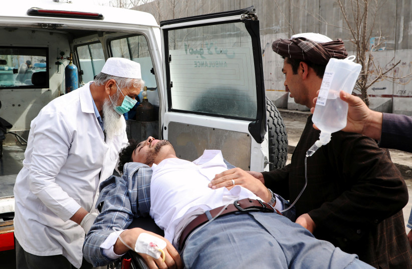Hospital workers carry an injured person after an attack in Kabul, Afghanistan March 6, 2020. (photo credit: OMAR SOBHANI / REUTERS)