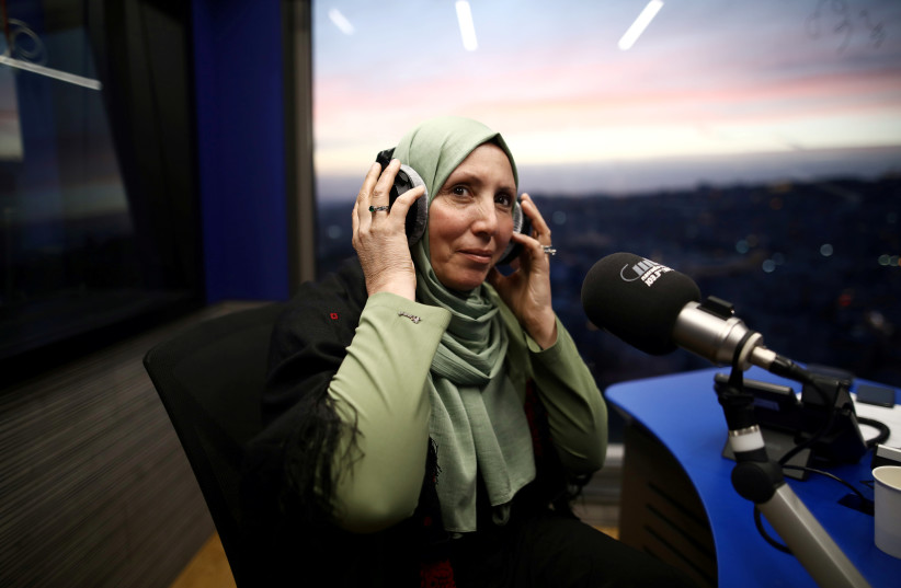 Iman Yassin Khatib, poised to become the first lawmaker in Israel's history to wear a hijab or head scarf, which she does as a Muslim, following results of her Arab Joint List party in Israel's election, participates in an interview in a radio show in Naz (photo credit: REUTERS)